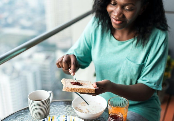 Black woman having breakfast at the balcony