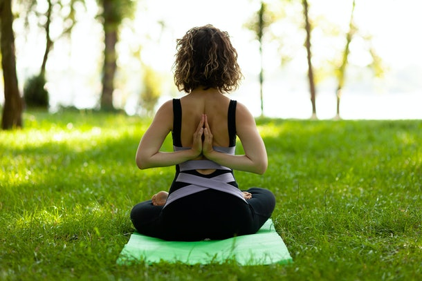 Beautiful smiling woman in morning park doing yoga and outdoor gymnastics. Green grass and rays of sun.