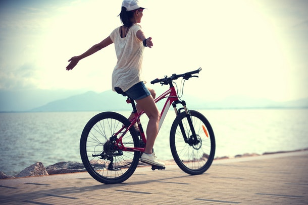 Woman riding a bike on sunny seaside with arms outstretched