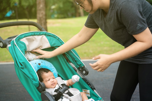 Mom walking in park with infant baby boy in stroller recreation nature