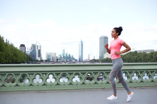 young woman running across westminster bridge.