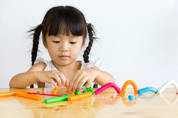 Asian girl playing plasticine.