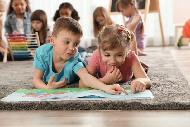 Cute kids reading book on floor while other children playing together in kindergarten