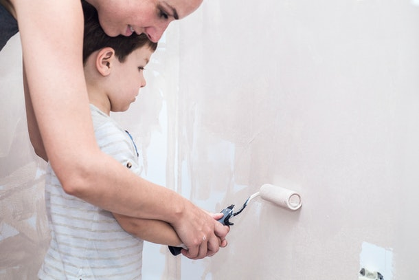Mom teachs her 3 years son painting with roller at home. Kids Helping House Chores concept