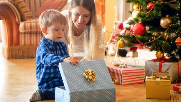 Toddler boy looking inside of CHristmas gift box with young mother