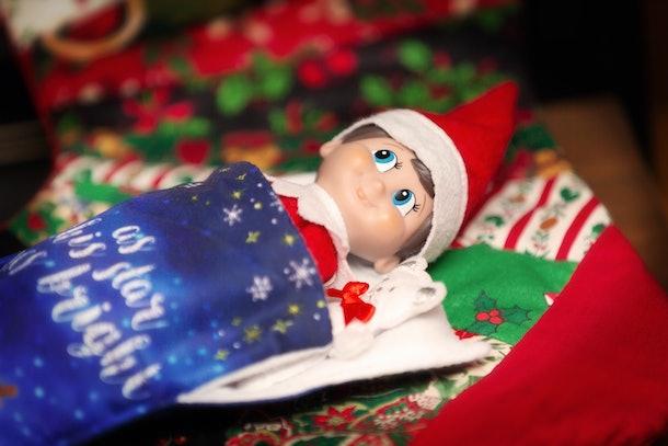 Elf on the shelf sleeping with teddy.