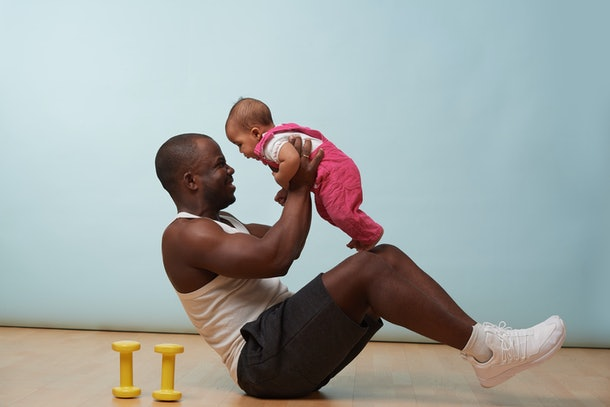 Handsome black young father is doing basic crunches while holding his tiny little baby daughter in hands. He is having trouble with additional weight.