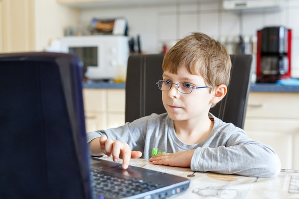 Little school kid boy with glasses playing game and surfing internet on computer. Child having fun with learning on pc. Education concept.