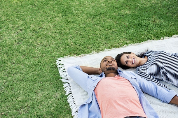Young multiethnic couple lying on blanket on grass. Latin woman with her african boyfriend relaxing on picnic blanket outdoor. Mature happy couple in love lying on grass with copy space.