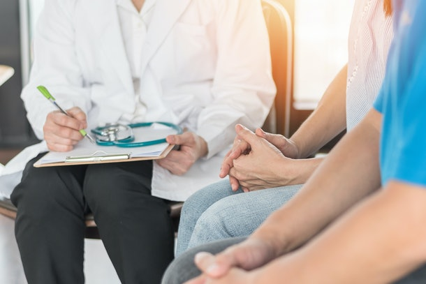 Patient couple consulting with psychologist doctor on marriage counseling, family medical health care therapy, In vitro fertilization IVF fertility treatment for infertility, or psychotherapy concept