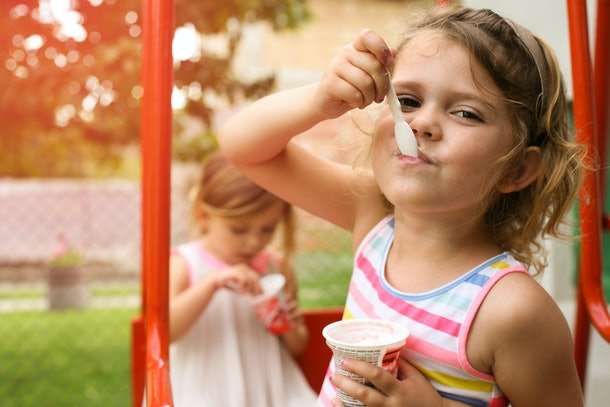 Cute little girl eating ice cream outside. Focus is on girl on foreground.