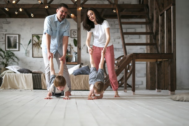 Dad and mom hold the children by the feet, the boys walk on their hands. Beautiful family with two sons in a studio apartment, Dad, Mom and two brother boys together, lifestyle in the real interior