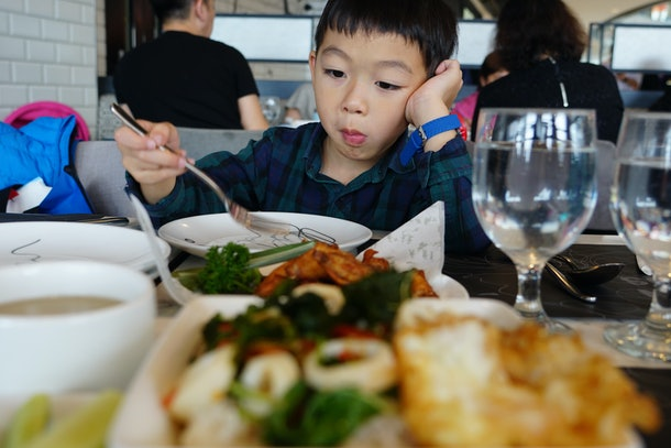 A cute Asian boy is feeling bored and picky eating in the restaurant.