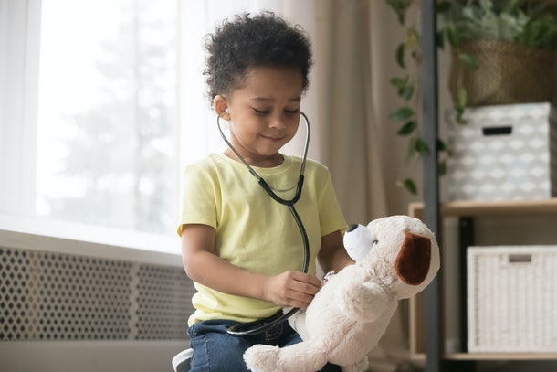 Cute little toddler african american boy playing funny game as doctor holding stethoscope listening to toy, mixed race black preschool child kid pretending nurse treating fluffy patient at home