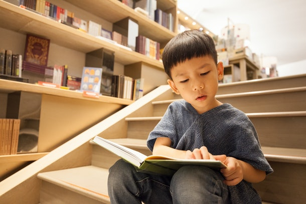 Portrait shot of an Asian pre-school boy sitting on the stairs, reading book in the library paying full attention. - Child's Brain Development - Cognitive concept.