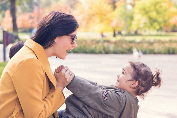 Happy mother with daughter talking and having fun in autumn park.