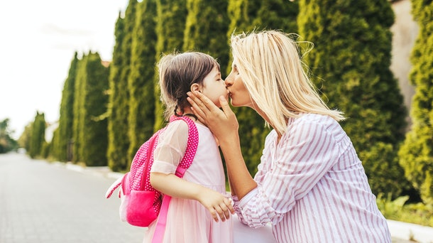 Horizontal portrait of happy cute little girl and beautiful mother embracing and kissing each other on sidewalkbefore the kindergraten. Mom with kid preschooler outdoor. Mother's day, school concept.