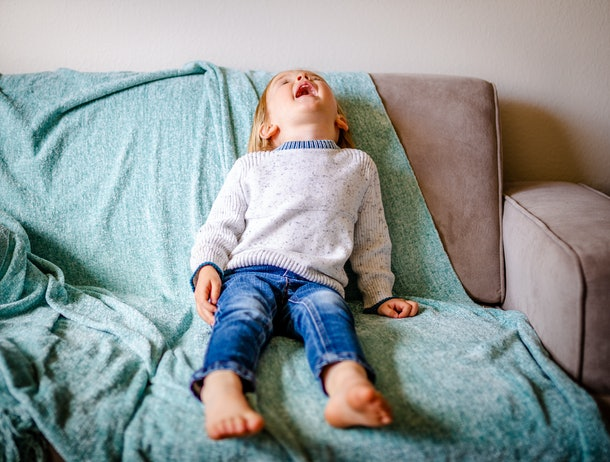 Cute toddler boy screams and cries on couch. Child is wearing blue jeans and white sweater while sitting on grey couch with blue throw blanket.