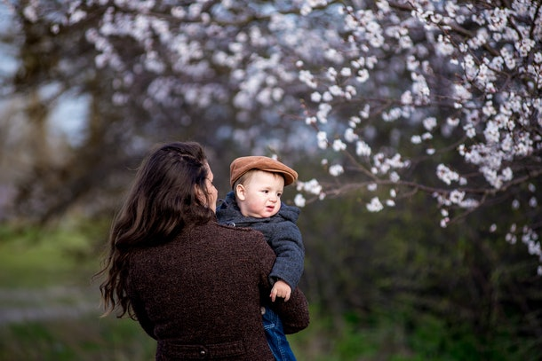Little baby boy with her young mother in the blossom garden. Spring