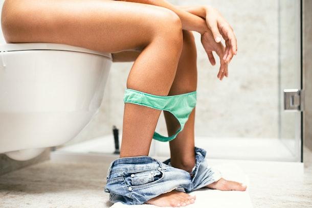 Woman in bathroom using toilet.