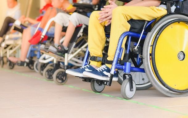 Disabled children sitting in wheelchairs, In line to wait for activities ,Close-Up yellow wheel, Life in the education age of disabled children.