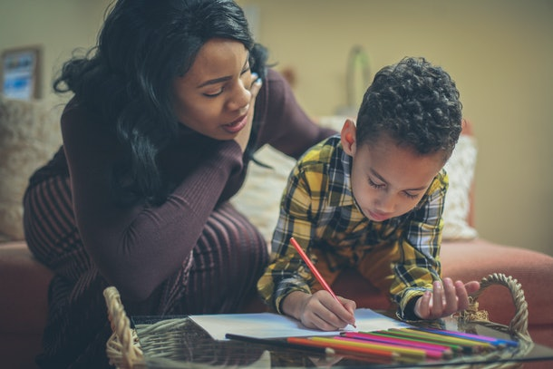 Preschool boy with his mother doing homework.