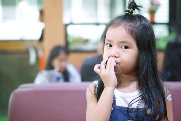 Asian child hungry or kid girl enjoy eating seaweed sushi delicious food or dessert with snack and happy for breakfast or lunch after take vaccine in japanese restaurant or preschool and food court