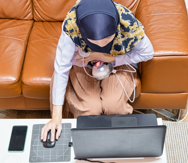 Busy young modern mother working with laptop while using automatically electric breast pump feeding for her baby. Top view.