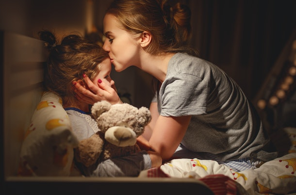 mother puts her daughter to bed and kisses her in the evening