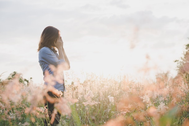 Sad woman standing in field with sunset background.