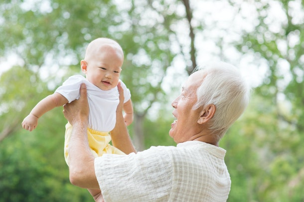 grandparent holding baby in the air