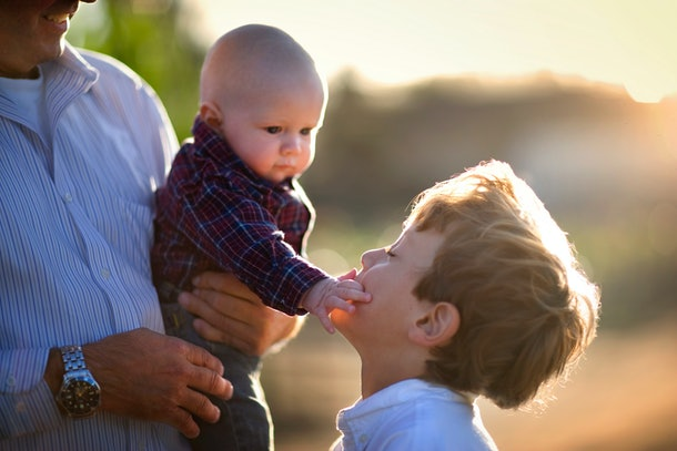 Young baby touching his older brother's face.