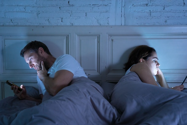 Young couple in bed late at night using smart phones obsessed with games, social media and apps ignoring each other in relationship communication problems and internet mobile addiction concept.