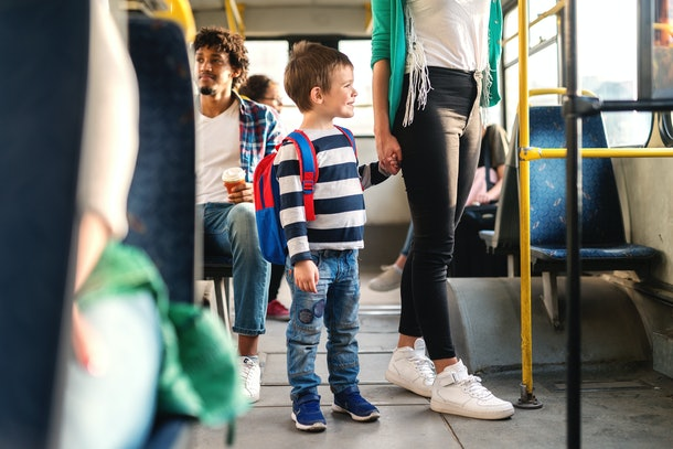 Mom holding son's hand and standing in the the public transportation.