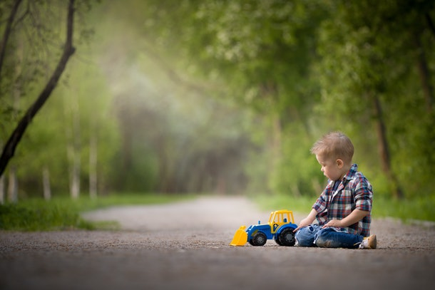 Portrait of cute kid boy sitting on the ground and playing with colourful tractor and sand in the park. Child playing outdoors. Lifestyle.