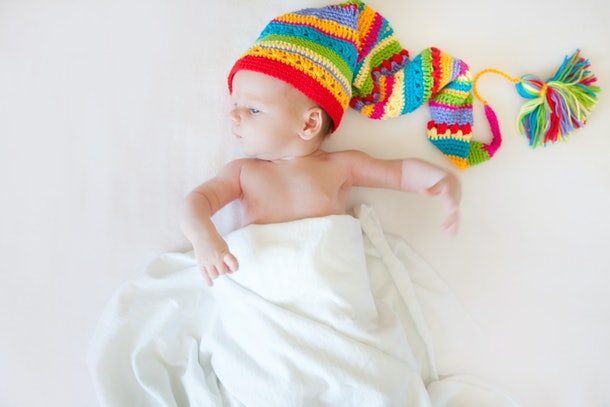 A baby one month is lying on a white background. Rainbow cap of the gnome.