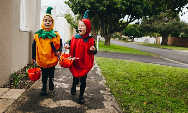 Identical twin sisters in halloween costume with halloween bucket walking on sidewalk. Halloween kids trick or treating.