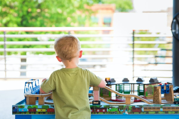 Toddler plays alone outside with a large wooden train set