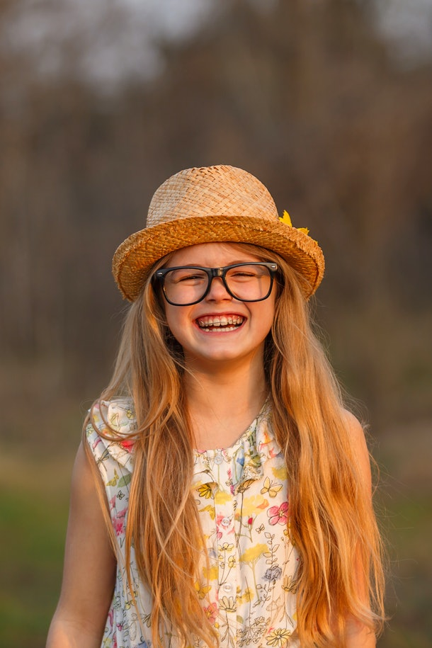 Portrait happy summer mood of joyful young girl in glasses, braces and straw hat, having fun.expressing positivity, joy, happiness, smiling