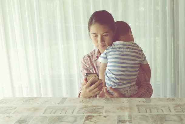 Portrait Mother holding baby boy while using smart phone at home. Vintage photo mom carrying son.