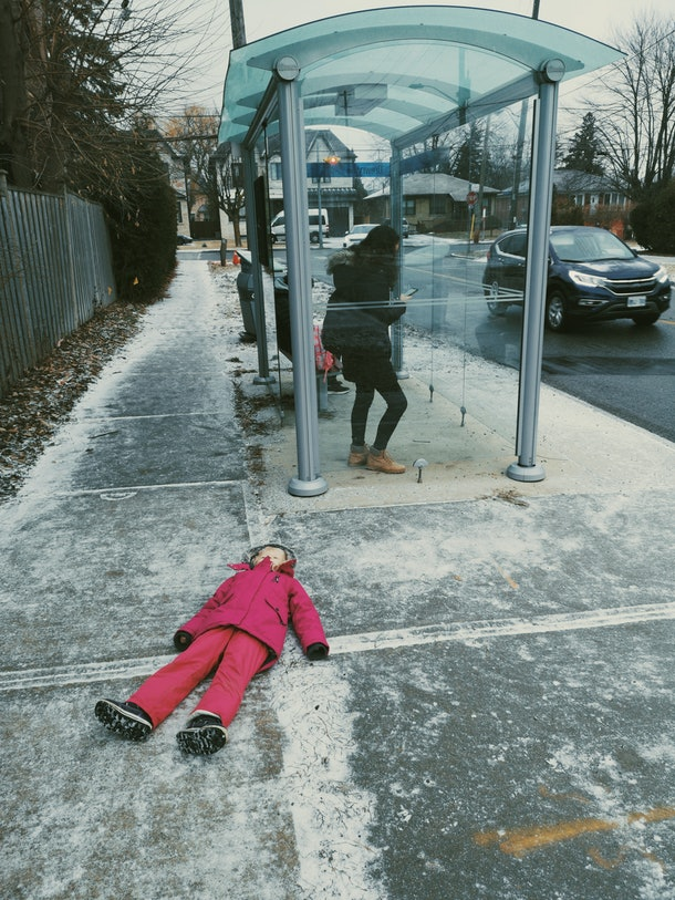 Child kid in tantrum bad mood lying on ground in city outside street not willing to obey parents. Parenting problems and challenges.
