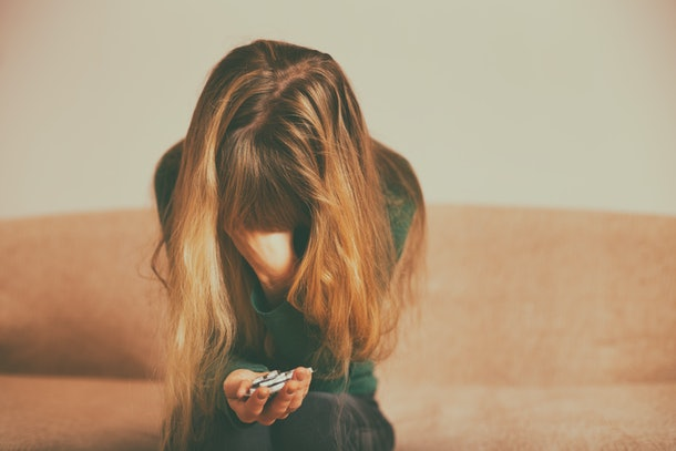 Depressed woman  holding pills while sitting alone at sofa .Toned image.