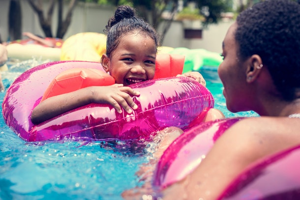 Closeup of black mother and daughter enjoying the pool with inflatable tubes