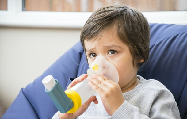 A boy have a problem with chest coughing holding inhaler mask by him self, Kid using the volumtic for breathing treatment, Healthcare and medicine concept