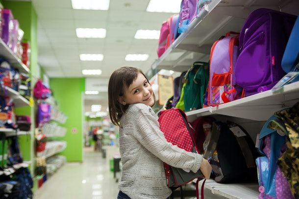 Portrait of   girl of 8 years in shop choosing  briefcase  for 