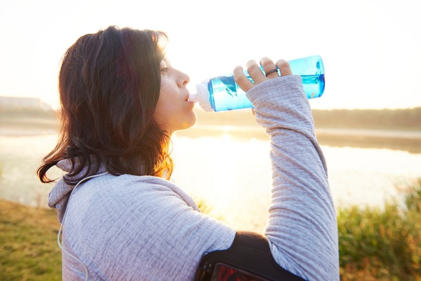 Woman drinking water after really hard workout