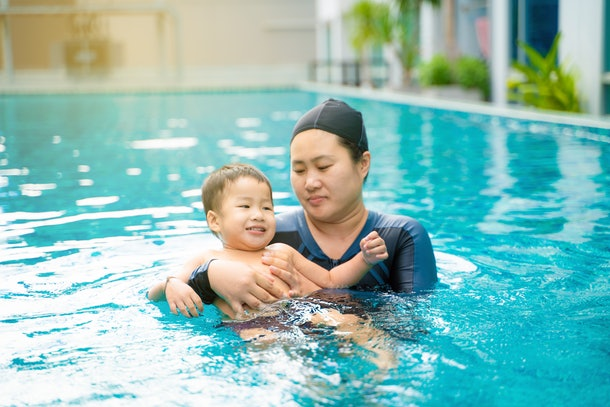 Child boy learn swimming with mom in swimming pool outdoor relax