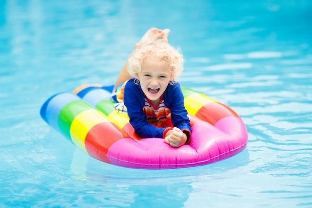 Happy child on inflatable ice cream float in outdoor swimming pool of tropical resort. Summer vacation with kids. Swim aids and wear for children. Water toys. Little boy floating on colorful raft.