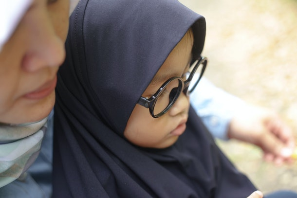 Portrait of happy Asian muslim mom and baby girl daugther talking and playing in the park, blurred with selective focus image