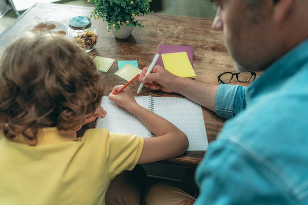 Mature father with little son writing in copybook and making school homework